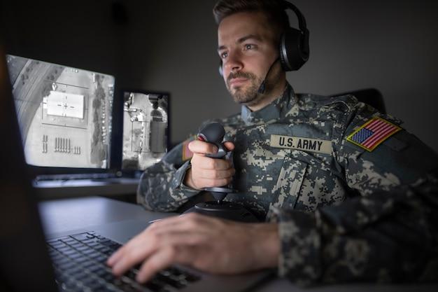 Amerikanischer soldat im hauptquartier des kontrollzentrums, der den drohnenangriff initialisiert