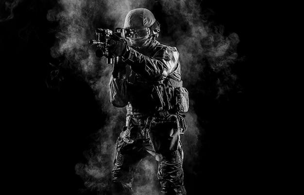 Amerikanischer soldat in kampfmunition mit waffe in den händen ausgerüsteter laservisiere ist in kampfreihenfolge. gemischte medien
