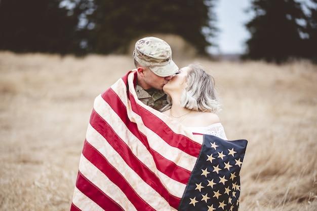 Amerikanischer soldat küsst seine liebende frau, während er in eine amerikanische flagge gehüllt wird