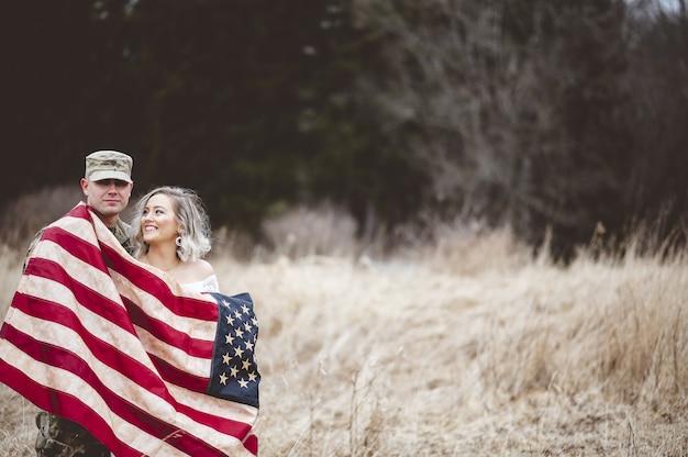 Amerikanischer soldat mit seiner lächelnden frau, eingewickelt in eine amerikanische flagge