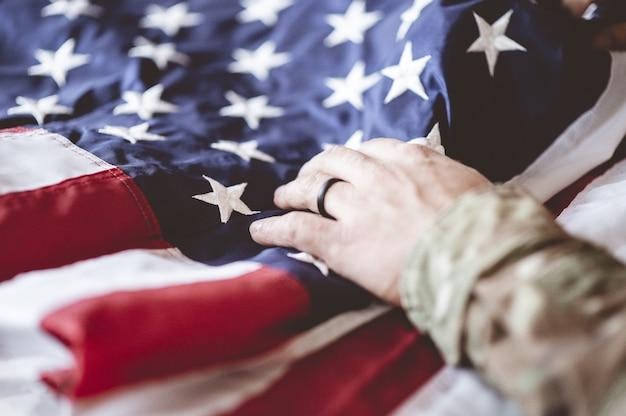 Amerikanischer soldat trauert und betet mit der amerikanischen flagge vor ihm