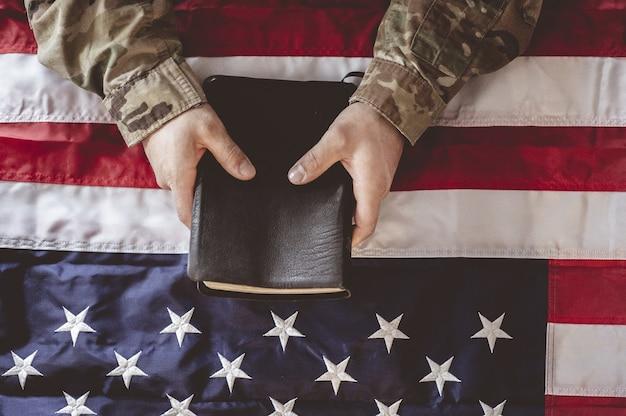 Amerikanischer soldat trauert und betet mit der bibel in seinen händen und der amerikanischen flagge