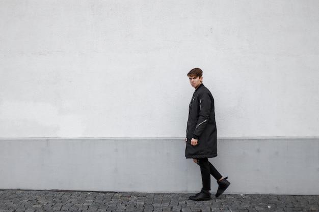 Amerikanischer stilvoller junger mann hipster in einer langen hellen jacke in trendigen schwarzen jeans mit einer frisur in trendigen turnschuhen entlang der straße in der nähe der vintage-wand. modischer moderner typ.
