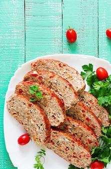 Amerikanisches essen. selbst gemachter hackfleischhackbraten mit ketschup und grünem pfeffer. fleischstück auf weißer platte. ansicht von oben. flach liegen
