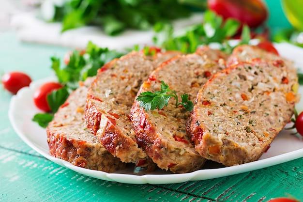 Amerikanisches essen. selbst gemachter hackfleischhackbraten mit ketschup und grünem pfeffer. fleischstück auf weißer platte.