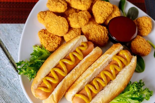 Amerikanisches fast food. hot dogs und hühnernuggets mit sauce.
