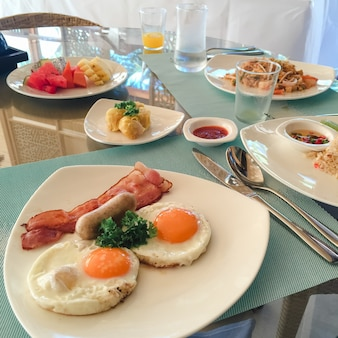 Amerikanisches frühstück. leckeres frühstück für einen. frau hände schneiden messer ei in einer pfanne. sicht von oben. spiegeleier. draufsicht