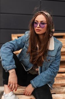 Amerikanisches hübsches modisches frauenmodell in stylischer lila brille in blauer vintage-denimjacke ruht auf holzpaletten in der nähe eines modernen gebäudes in der stadt. schönes hippie-mädchen. beiläufige art und weise.