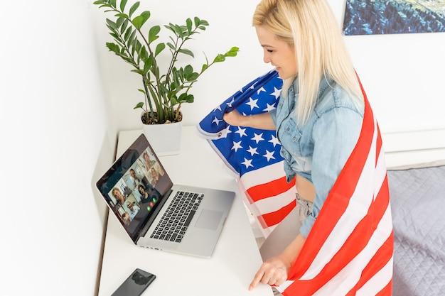 Amerikanisches junges mädchen live-streaming mit ihrem laptop und der usa-flagge auf ihr