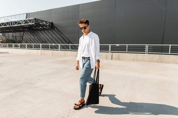 Amerikanisches junges mann-modemodell in trendigen jeans in einem stilvollen hemd in modischen sandalen in der sonnenbrille mit tasche geht nahe einem grauen gebäude.