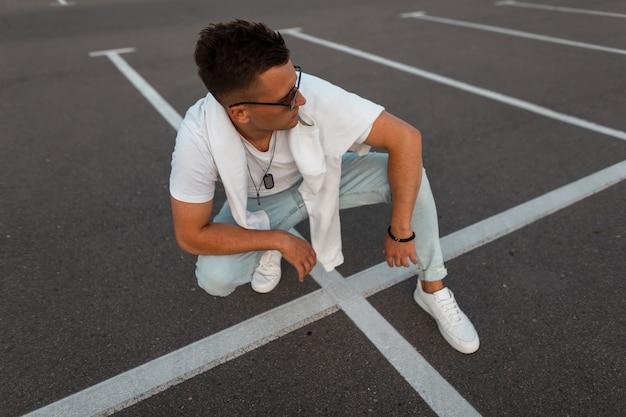 Amerikanisches junges mannmodell in modischer sonnenbrille in vintage blue jeans in einem stilvollen weißen t-shirt in turnschuhen sitzt auf dem bürgersteig. städtischer typ, der sich draußen ausruht. sommerjugendmode.
