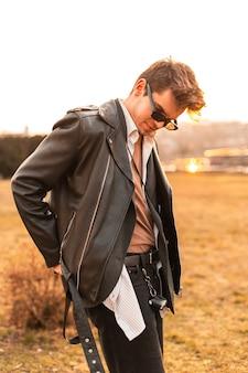 Amerikanisches junges mannmodell in stilvoller sonnenbrille in modischer schwarzer lederjacke im hemd entspannt sich abends bei strahlender sonne im freien. sexy hipster-typ genießt orangefarbenes sonnenlicht bei sonnenuntergang. legerer stil.