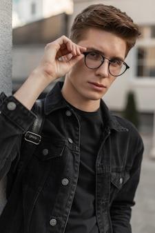 Amerikanisches mann-mode-modell setzt im freien eine vintage-brille auf. street trendy portrait modischer junger kerl in stilvoller schwarzer jeansjacke mit frisur in der nähe von weißem gebäude in der stadt.