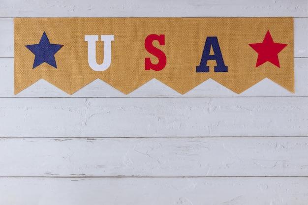 Amerikanisches symbol, das feiertags-usa-wort der buchstaben mit veteranentag-gedenktag-arbeitstag-unabhängigkeitstag auf holzhintergrund feiert