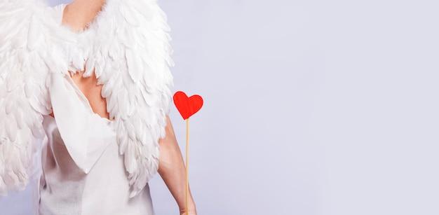 Amor mit flügeln steht mit dem rücken und hält in der hand einen pfeil mit einem roten herzen