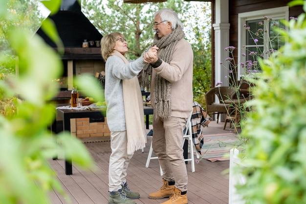Amouröses älteres paar in warmer freizeitkleidung tanzt auf dem holzboden der terrasse neben ihrem landhaus gegen servierten tisch und kamin