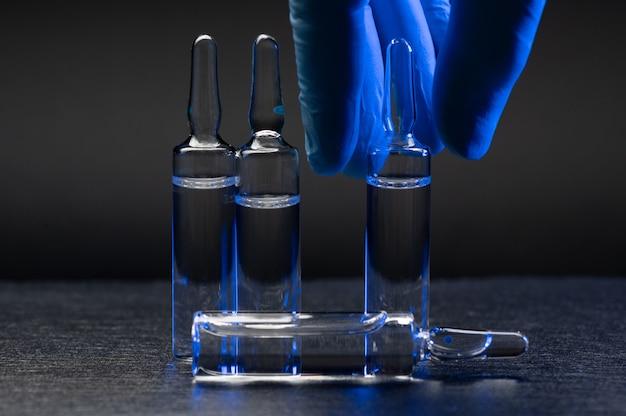 Ampulle mit einem impfstoff in der hand eines mediziners in gummihandschuhen
