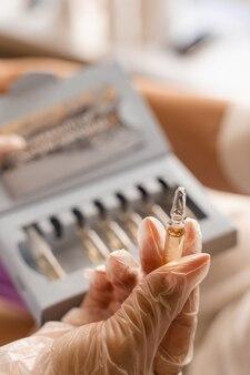 Ampulle mit vitaminen in den händen einer kosmetikerin.