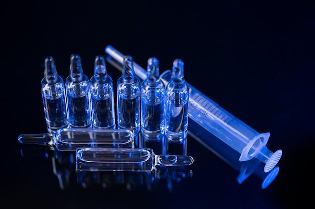 Ampullen zur injektion und spritze auf dem dunklen hochglanztisch als konzept für den kampf gegen das coronavirus mit kopierraum