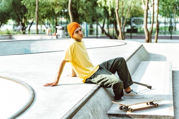 Amputierter skater, der zeit im skatepark verbringt. konzept über behinderung und sport