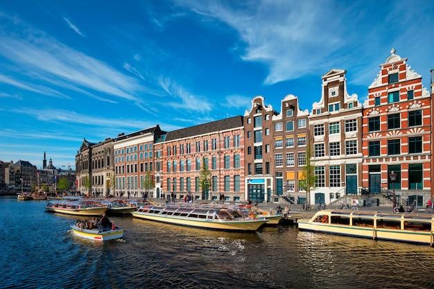 Amsterdamer aussichtskanal mit bootsbrücke und alten häusern