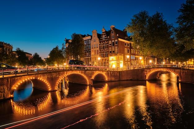 Amsterdamer kanalbrücke und mittelalterliche häuser am abend
