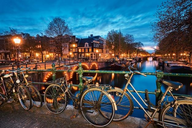 Amterdamer kanal, brücke und mittelalterliche häuser am abend