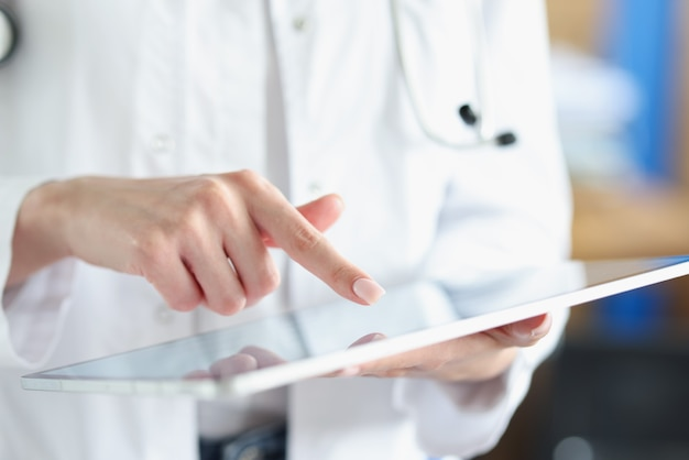 Amtsarztarzt zeigt mit dem finger auf tablet