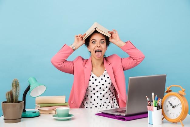 Amüsante frau, die buch hält und ihre zunge herausstreckt, während sie am schreibtisch arbeitet, isoliert über blauer wand?