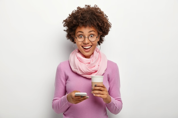 Amüsiert angenehm aussehende lockige frau benutzt handy und trinkt kaffee zum mitnehmen, ist gut gelaunt, surft in den sozialen medien