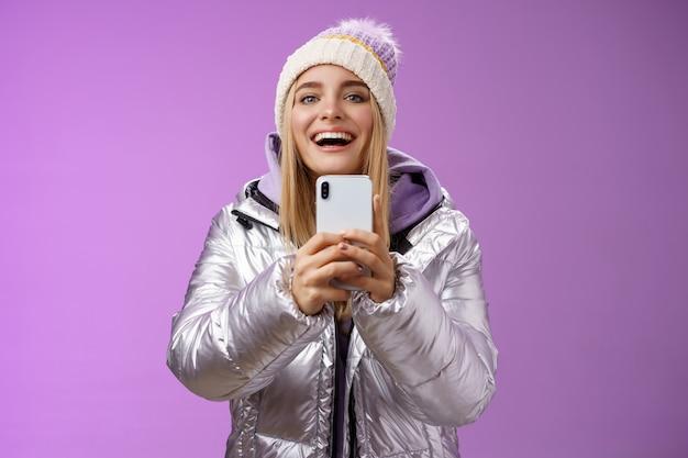 Amüsiert aufgeregt attraktive blonde freundin hält smartphone hoch aufnahme video freund schritt snowboard zum ersten mal erinnerungen mobile kamera erfassen glücklich lila hintergrund.