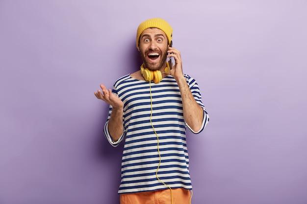 Amüsiert freudiger hipster hält handy in der nähe von ohr, hat lustige telefongespräche, trägt gelben hut und gestreiften pullover