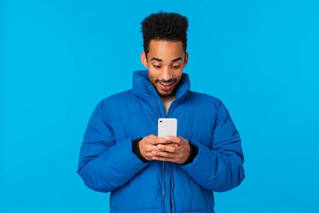 Amüsiert und unterhalten afroamerikaner kerl lächelnd sehen mädchen antwortete auf seine nachricht