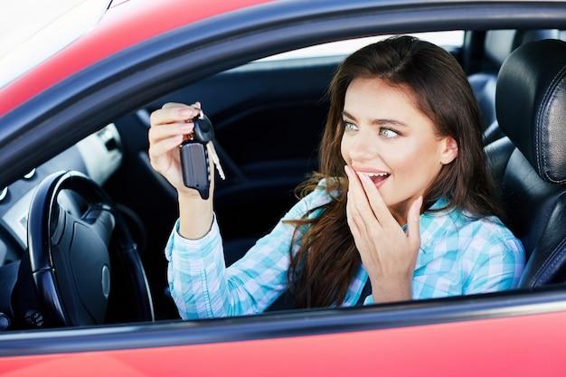 Amüsierte brünette frau, die rotes auto fährt und auto kauft. glücklicher besitzer des neuen autos, schlüssel betrachtend, vom auto und lächelnd. kopf und schultern, glücklicher fahrer