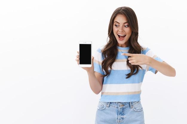 Amüsierte fröhliche junge frau stellt smartphone-app vor, hält das handy, zeigt und schaut auf das display, lächelt aufgeregt und empfiehlt eine tolle anwendung, online-shop