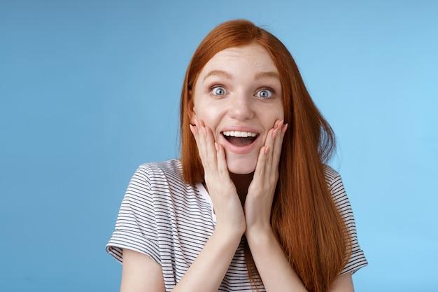 Amüsierte glückliche verträumte junge aufgeregte rothaarige weibliche fan, die faszinierte kamera lächelnde bewunderung aussah, begeisterte berührungsgesicht begeisterte emotionale, fröhliche überraschung, blauer hintergrund.