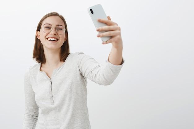 Amüsierte gut aussehende europäische studentin mit kurzen braunen haaren in transparenten gläsern, die smartphone halten und lachen und auf gerätebildschirm schauen, der über videobotschaften über graue wand spricht