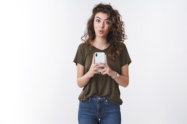 Amüsierte gut aussehende junge armenische lockige frau beeindruckte tolle coole smartphone-kamera, die fotos macht, sagen, wow falten die lippen überrascht, erfreut, gute aufnahmen zu machen, stehender weißer hintergrund