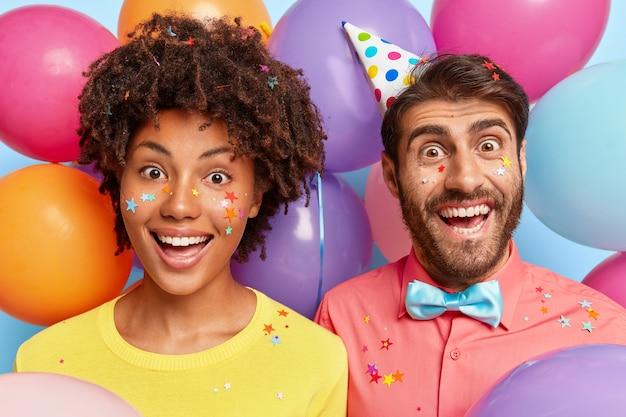 Amüsiertes fröhliches junges paar posiert umgeben von bunten luftballons zum geburtstag