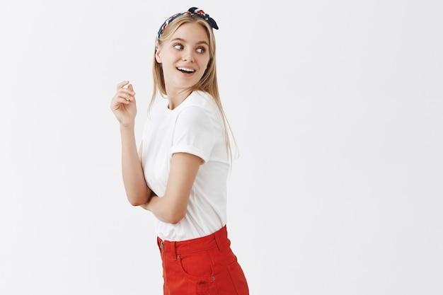 Amüsiertes und neugieriges junges blondes mädchen, das gegen die weiße wand aufwirft