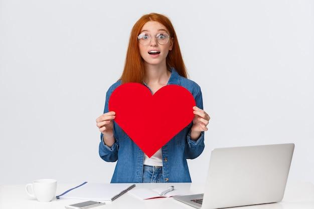 Amüsiertes und verträumtes überraschtes rothaariges mädchen erhielt großes rotes valentinstagherz von kollegen