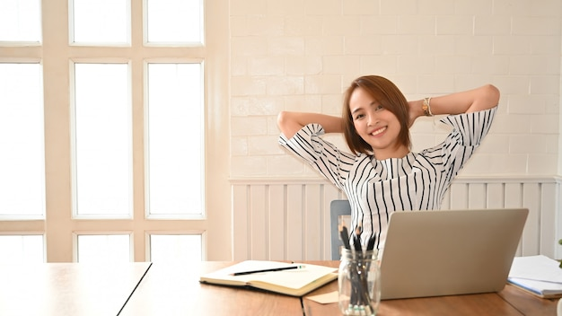An bequemen in den bürofrauenhänden hinter kopf sich entspannen, die glückliche frau, die im büro stillsteht, stellte nach der arbeit zufrieden
