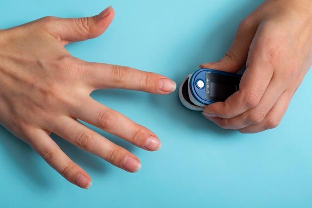 An der hand der frau befindet sich ein pulsoximeter. ein pulsoximeter zur messung der herzfrequenz und des sauerstoffgehalts. covid-19