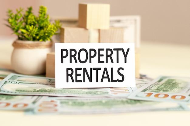 An der wand aus papiergeld und holzwürfeln befindet sich eine weiße papierkarte mit dem text property rentals. unternehmenskonzept.