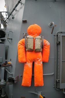 An der wand eines kriegsschiffs hängt eine orangefarbene trainingspuppe. die schaufensterpuppe ist sehr schäbig.