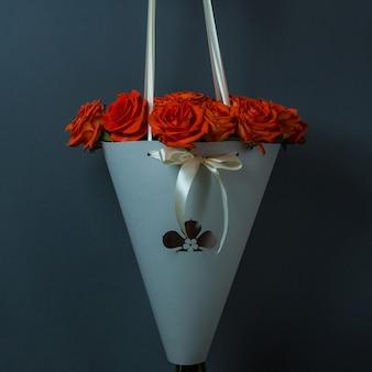 An der wand hing ein strauß roter rosen, der ein bouquet aus papier bewarb
