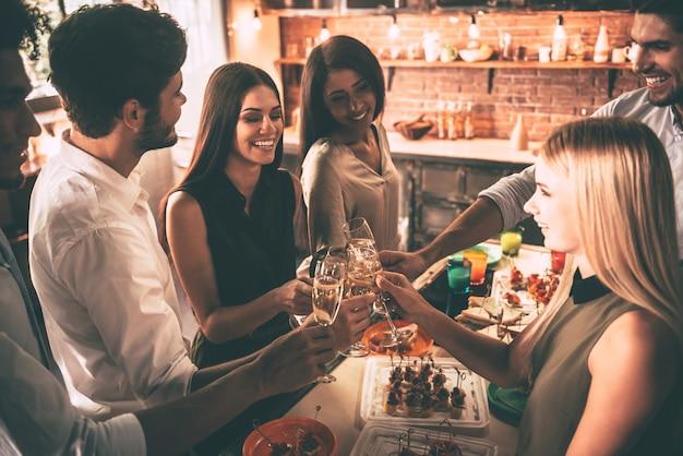 An die besten freunde aller zeiten! draufsicht auf fröhliche junge leute, die mit sektflöten jubeln und glücklich aussehen, während sie in der küche feiern?