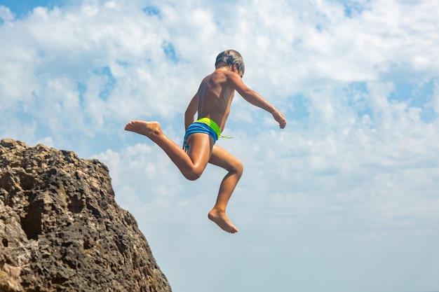 An einem heißen sommertag springt ein junge von der klippe ins meer. urlaub am strand. das konzept des aktiven tourismus und der erholung
