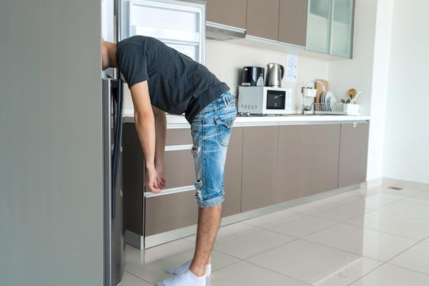 An einem heißen tag kühlt sich der typ mit dem kopf im kühlschrank ab. klimaanlage kaputt.