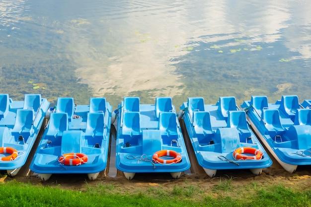 An einem sonnigen tag parkten tretboote aus kunststoff am seeufer.